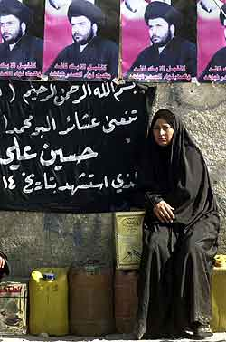 En kvinne sitter under et portrett av sjialederen Moqtada al-Sadr i Sadr-byen i Bagdad. Foto: Karim Kadim, AP