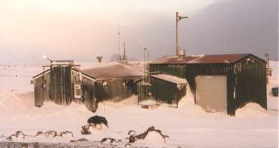 Den meteorologiske stasjonen på Jan Mayen, med stasjonshunden Sondre i forgrunnen. Foto: Bernt Olsen