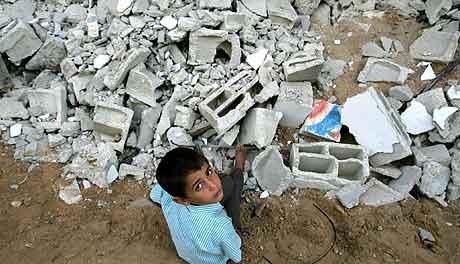 En palestinsk gutt sitter i en ruinene av et ødelagt hjem på Gasastripen. Foto: Odd Andersen, AFP
