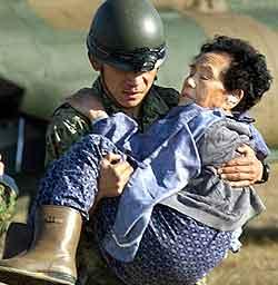 En eldre kvinne evakueres. Foto: Reuters