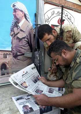 To palestinere leser avisreportasjen om helsetilstaden til Yasser Arafat i Hein el-Hilweh i Sør-Libanon. (Foto: Mohammed Zaatari / AP / Scanpix)