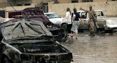 En vakt fra den irakiske nasjonalgarden viser vei for to kvinner etter bilbombeeksplosjonen i sentrum av Bagdad. Også en vannledning ble sprengt i stykker i eksplosjonen.  (Foto: Marwab Naamani  / AFP / Scanpix)