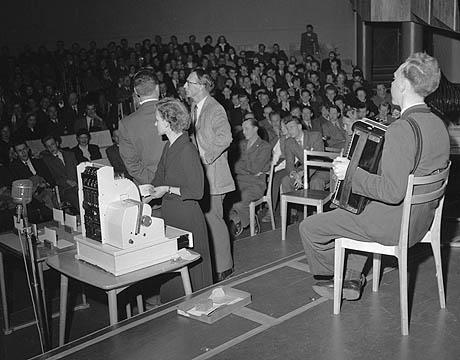 """NRKs knall-suksess """"Det Spørs"""" ledet av Rolf Kirkvaag. Alf Blyverket sørger for musikken og Bibbi Asmuss for utbetalingene. I bakgrunnen Kirkvaag (tv) sammen med en av kandidatene. Foto: Storløkken/Aktuell/Scanpix"""