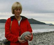 Torill Helene Molnes lagar kunst av stein frå si eiga strand. Foto: NRK.