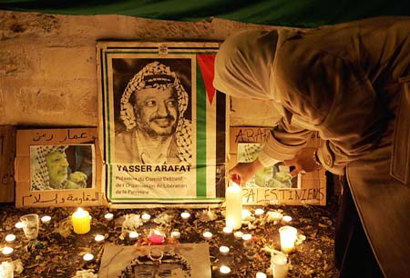 En kvinne tenner et lys for Yasir Arafat utenfor det franske militærsykehuset sør for Paris. (Foto: P.Andrieu, AFP)