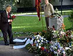 Anna Lindhs enkemann, Bo Holmberg, legger blomster på graven 11.september i år, ett år etter drapet. Foto: Christan Oernberg, AFP