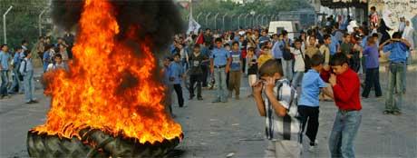SORG: Palestinske ungdommer viste sin sorg ved å sette fyr på lastebildekk, og røyklegge gatene i flyktningeleiren Jebaliya. (Foto: AP Photo/Adel Hana)