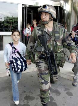 En fransk soldat hånd i hånd med ei jente som evakueres fra et hotell i Abidjan i dag. (Foto: P. Guyot, AFP)