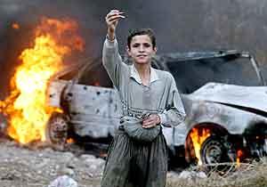 En irakisk gutt viser frem kuler nær en brennende bil i Bagdad fredag. Foto: Ceerwan Aziz , Reuters