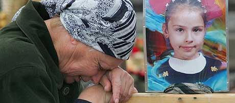 EN BY I SORG: En ukjent slektning av Maria Urmanova (9), som ble drept under gisselaksjonen, sørger ved graven 13. oktober. (Foto: Ivan Sekretarev/AP)