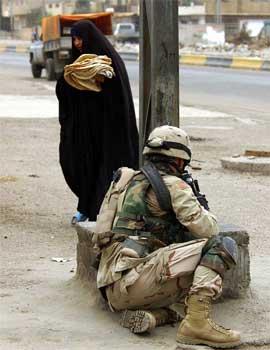 En kvinne i Bagdad passerer en kampklar amerikansk soldat. (Foto: AP/Scanpix)