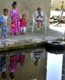 Barn ved en oversvømmet gate i Sadr-byen i Bagdad. (Foto: Scanpix / AP)