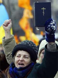 Kvinnen vifter med Bibelen under demonstrasjonen i Kiev.(Foto:Scanpix)