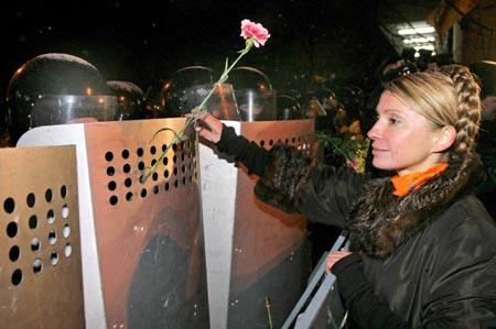 Yulia Tymosjenko, medlem av nasjonalforsamlingen og en av Justsjenkos viktigste allierte, markerer sine fredelige hensikter overfor opprørspolitiet. (Foto: Reuters)