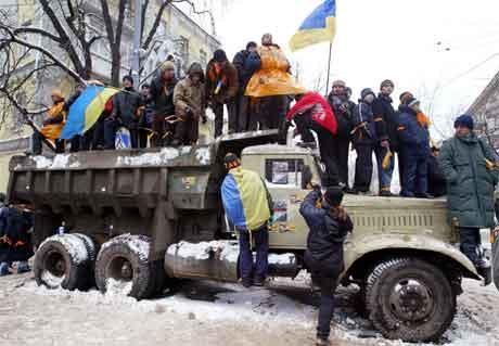 Store folkemengder blokkerer inngangen til regjeringsbygningane i Kiev. (Foto: AFP/Reuters)