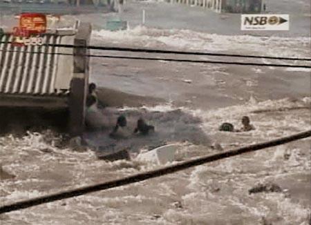 Folk forsøker å klamre seg til en bygning på østkysten av Sri Lanka, som ble hardest rammet av flodbølgene. (Foto: SLRC)