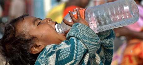 VANNBEHOV: Et indisk barn får etterlengtet vann i en leir i Madras i dag. (Foto: Scanpix / Reuters / Babu)