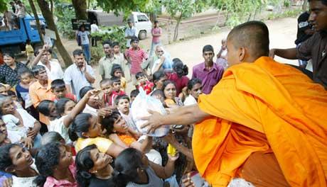 Buddhistmunker deler ut mat til overlevende i Ambalantota. Andre måtte begrave de som mistet livet da toget ble tatt, noe som ifølge BBC gjør episoden til historiens verste togulykke (Foto: Thomas White /Reuters / Scanpix)