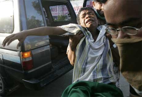 En indonesisk gutt må bæres inn til sykehus i Banda Aceh. (Foto: AP/Scanpix)