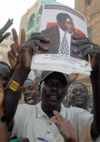 FEIRER: En sør-sudans mann feirer fredsavtalen med bildene av SPLM/A leder John Garang i hendene. Foto: AFP/Scanpix.