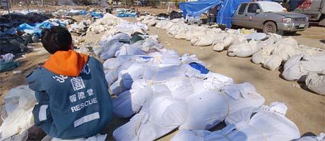 En thailandsk hjelpearbeider venter på at ofre for flomkatastrofen skal transporteres fra Takua Pa (Foto: AFP /Romeo Gacad)