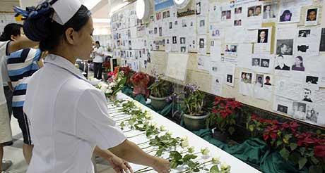 «WALL OF LOVE»: En thailandsk sykepleier legger ned en hvit rose foran en vegg med bilder av savnede etter flodbølgen 2. juledag. Veggen med bilder går under navnet «The wall of love». (Foto: Richard Vogel/AP)