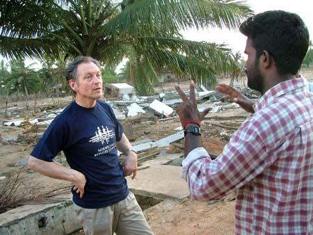 Det ble en sterk opplevelse for prosjektleder Rolf Moi på befaring i Trincomalee. En lokal fisker viser med fingeren at åtte av ti i hans familie døde i katastrofen. (Foto: Torgrim Halvari, NRK)