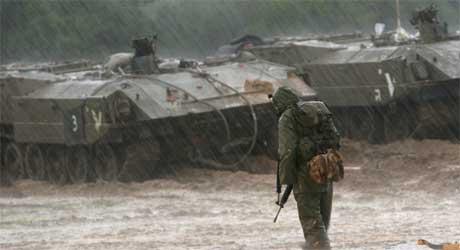 I kraftig regn betrakter en soldat israelske stridsvogner i det området der tolv andre soldater ble såret i dag (Scanpix/AFP)