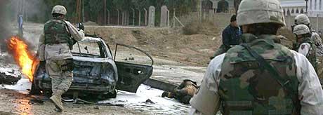 NOK EN BILBOMBE: Stadige terrorhandlinger tyder på at valget i Irak vil bli utsatt. Her rydder amerikanske soldater er område i byen Baquba, etter at en bombe eksploderte 5. januar 2005. Minst seks personer ble drept. (Foto: Ali Yussef/AFP)