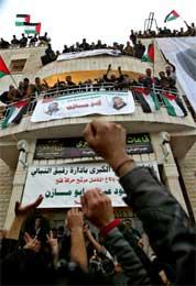 Tilhengerne hilser Abbas som hever armene på balkongen med bilder av ham selv og Arafat (Scanpix/AP)