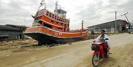 FRYKTER MYNDIGHETENE: Burmesere uten oppholdstillatelse våger trolig ikke identifisere døde slektninger etter flodbølgen. Bildet viser en fiskebåt som endte opp langt oppe på land etter flodbølgen 2. juledag. (Foto: Peter Parks/AFP)