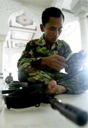 I mange av fredagens bønner ble det nok bedt om fred, men denne soldaten, som leser Koranen, har også geværet sitt med seg (Scanpix/Reuters)