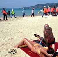 Turister og oppryddningsarbeidere på stranden i Phuket i Thailand. (Foto: Reuters/Scanpix)