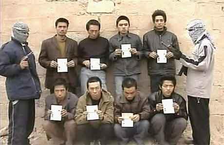 Dette bildet, som ble lagt ut på en internettside 18 januar 2005, viser to gisseltakere på hver sin side av de åtte bortførte kineserne. (FOTO: AFP)