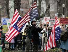 Mange er skeptiske til nye år med Bush. Her holder demonstranter i Portland flagget opp-ned (Scanpix/AP)