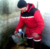 Vannprøver tas oppi en plastkanne.