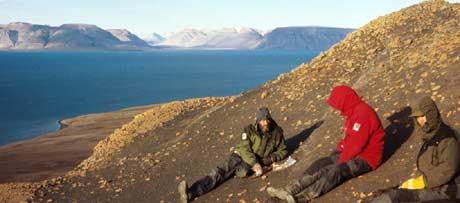Noen fossiljegere setter seg for å studere kartet(Foto: Roger Myren/NRK)