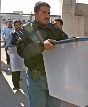 Irakisk politi frakter boksene som stemmesedelene skal puttes i. (Foto: Scanpix / Reuters / Atef Hassan)