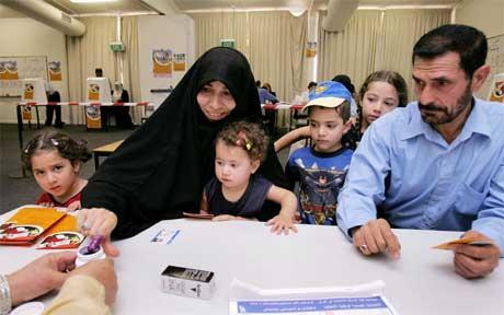 En irakisk kvinne har tatt med seg familien til et valglokale i Melbourne i Australia. (Foto: AFP/Scanpix)