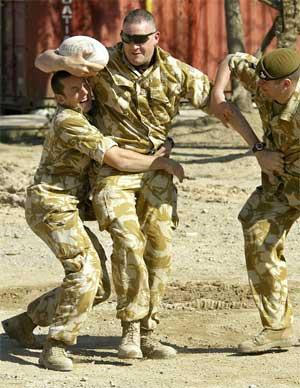 Britiske soldater lader opp foran valget med en rugbykamp ved Saddam Husseins palass i Basra. (Foto: Scanpix / AP / Odd Andersen)