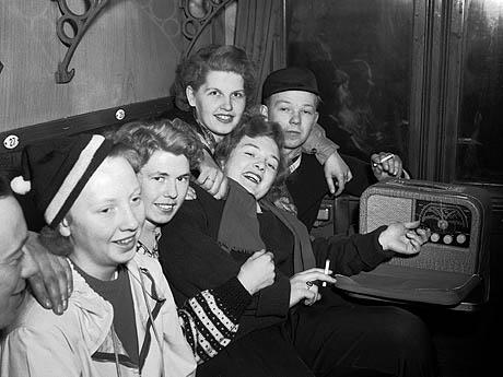 En glad ungdomsgjeng ombord i en røykekupe på Bergenstoget like før avgang fra Østbanen i 1952. En Kurér reiseradio og en sigarett hører med til kosen. Foto: NTB / Scanpix