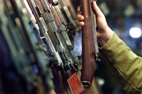 Politimann i Belfast undersøker et av de mange hundre våpnene som er fratatt IRA i de siste 20 år (Scanpix / Reuters)