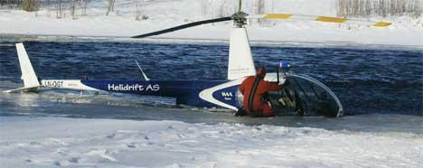 Det norske helikopteret som styrtet i en elv utenfor Hagfors i Värmland under innledningen til Rally Sverige den 7. februar 2004 blir her løftet ut av elven av en norskt helikopter lørdag. Foto: Olle Persson / SCANPIX SVERIGE