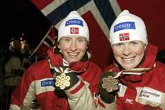 En glad verdensmester Marit Bjørgen (t.v.) og bronsevinner Hilde Gjermundshaug Pedersen med VM-medaljene etter sprinten i Val di Fiemme. (Foto: Terje Bendiksby / SCANPIX)