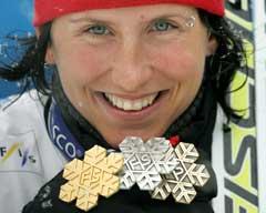 Marit Bjørgen viser frem sine tre VM-medaljer. (Foto: AFP/Scanpix)