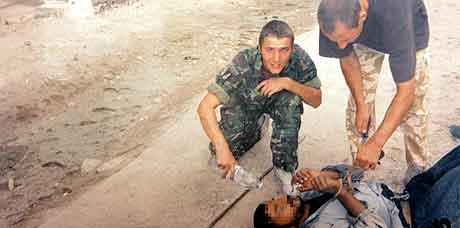 På bildet sees en av de dømte,  Daniel Kenyon, t.h. bøye seg over en irakisk fange som ligger nede. (AFP)