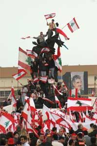 Demonstranter med flagg klatret opp på Martyrstautuen (Scanpix/Reuters)