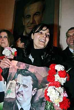 En syrisk kvinne bærer et bilde av presidenten under feiringene av at soldatene er kommet hjem. Foto: Khaled al-Hariri, Reuters