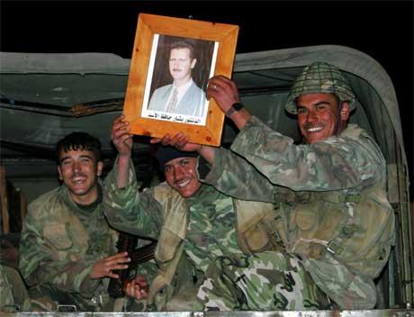 Syriske tropper holder et bilde av president Bashar al Assad .(Foto:Reuters/Scanpix)
