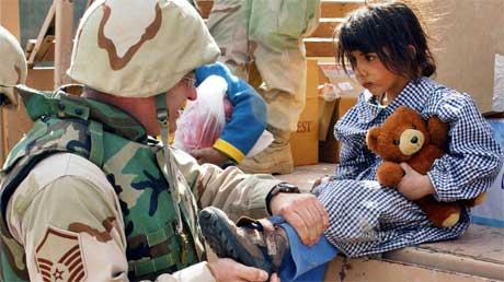 En amerikansk soldat gir nye sko til en irakisk beduinjente. (Foto: Scanpix / Reuters)
